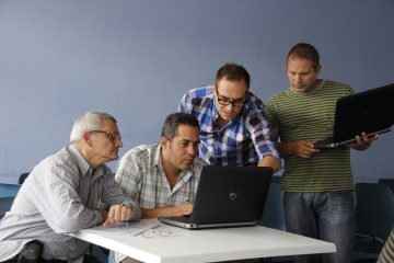 Four men at a desk look at the screen of a laptop, one of the men pointing at something on the screen.